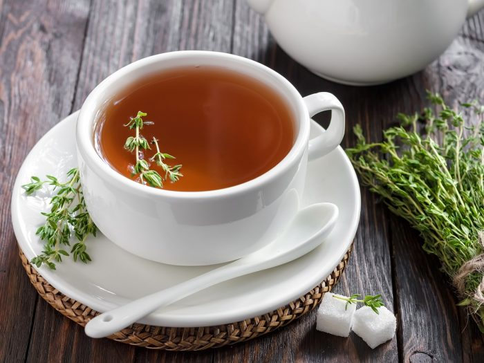 A white cup of thyme tea with sugar cubes and thyme herb on a wooden background