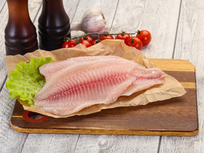 Tilapia fillets on parchment paper, with lettuce, cherry tomatoes, and garlic in the background