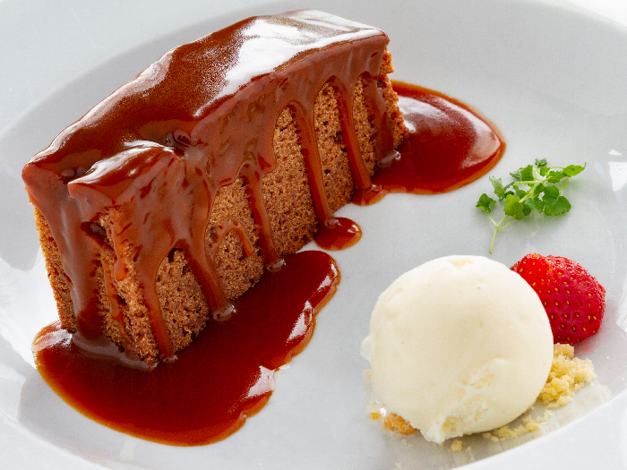 Plate with a slice od sticky tofee pudding, toffee sauce on top and a scoop of vanilla ice cream.