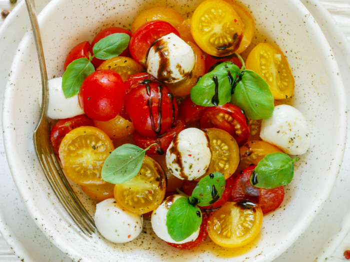 A yellow and red tomato salad in a white bowl with a fork