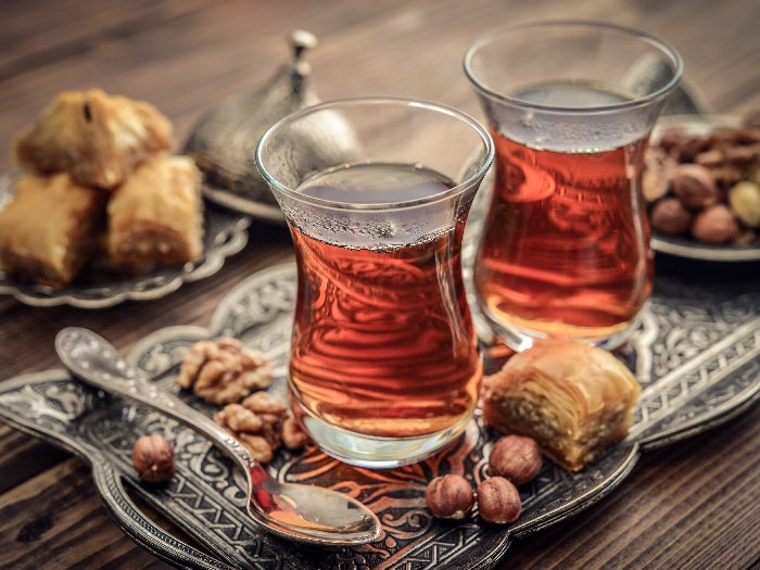 A cup of Turkish tea served in traditional style with baklava and nuts in the background