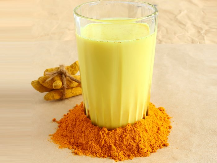 A glass filled with turmeric milk, surrounded by turmeric powder around its surface