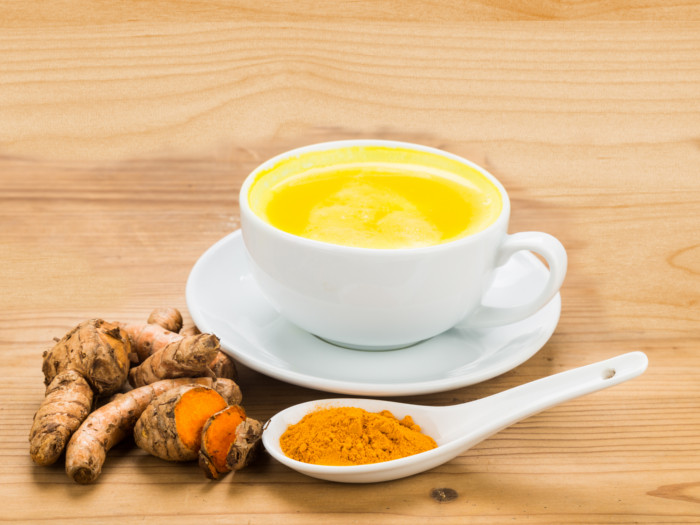 A small cup of turmeric beverage and turmeric roots with a spoonful of turmeric powder near it