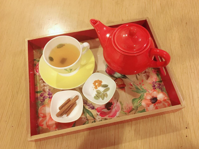 Flatlay picture of a red teapot, two small bowls with spices and a cup and saucer of tea