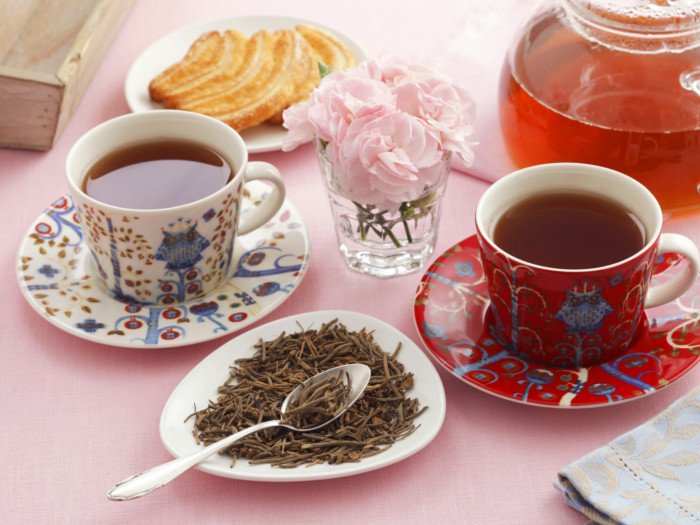 Traditional cups with valerian tea, valerian tea leaves, and a teapot on a table