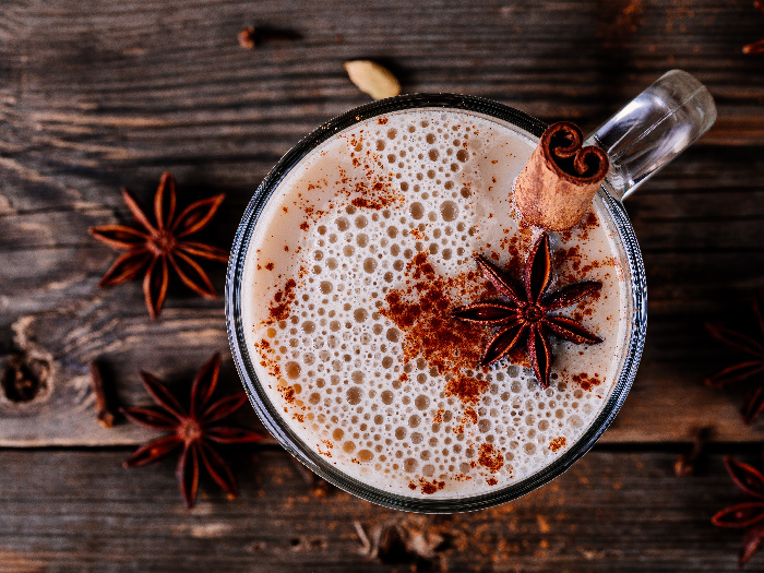 Homemade Chai Tea Latte with anise and cinnamon stick in glass mug on wooden rustic background