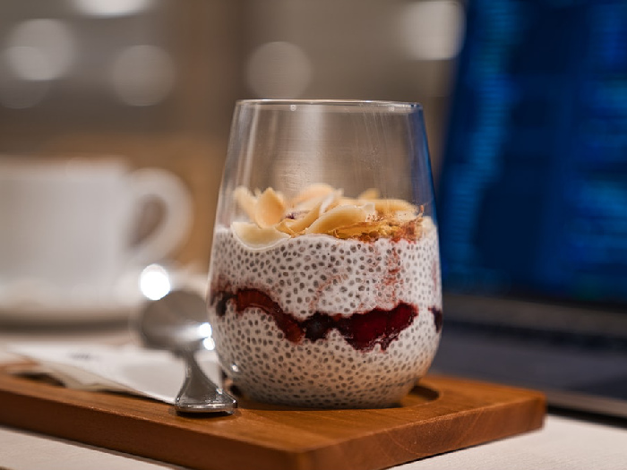 A delicious glass of vanilla chia pudding garnished with fresh fruits, kept atop a wooden slab, next to a spoon
