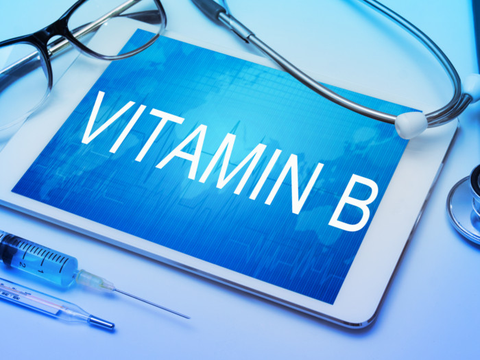 VITAMIN B' written on a tab surrounded by a stethoscope, injection, and glasses, placed on a blue surface.