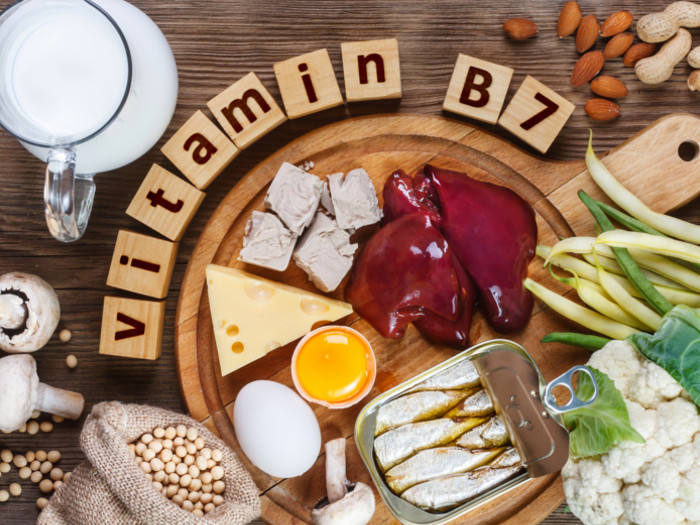 Flatline view of food containing vitamin B7: liver, canned fish, egg, jar of milk, mushroom, beans, nuts, and vegetables.