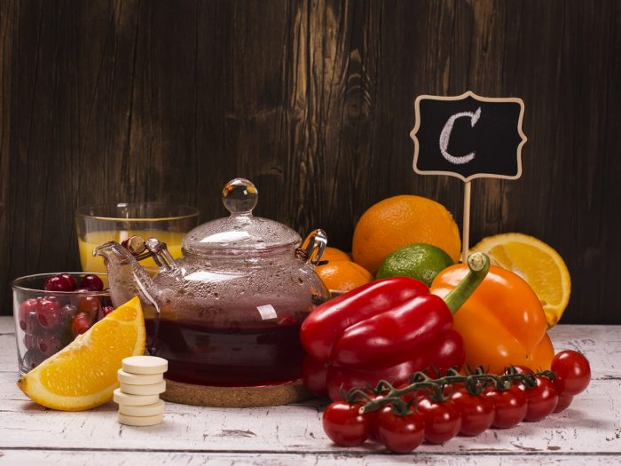 Foods rich in vitamin C (whole and halved sweet limes, red and yellow chili pepper, red cherries) with glasses of sweet lime juice and cherries on a wooden table