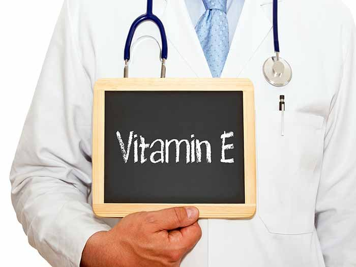 Doctor with a stethoscope, holding a board that says vitamin E