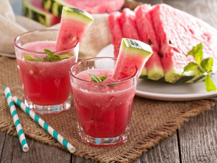 Two small glasses of watermelon juice accompanied by straws and watermelon slices on a table