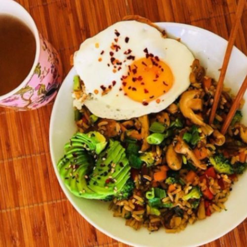 Stir fried vegetables sauteed with rice, served with avocado and eggs to the side, placed atop a wooden table