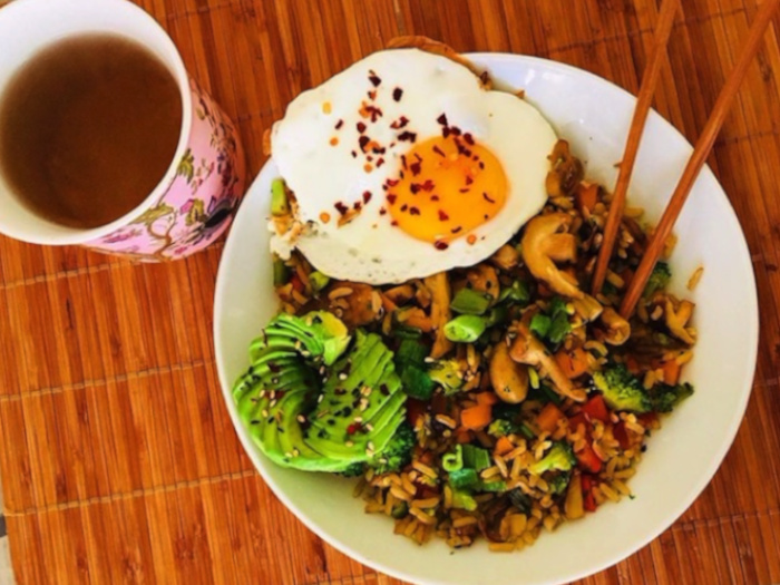 Stir-fried vegetables sauteed with rice, served with avocado and eggs to the side, placed atop a wooden table