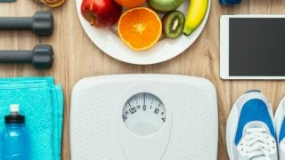 Diet and weight loss for health care - dumbbells, measuring tape, canvas shoes, fruits, towel, bottle, white scale, & digital tablet on a wooden table
