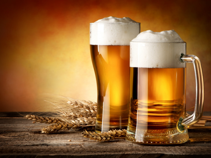 Glasses of wheat beer and wheat ears on a wooden table