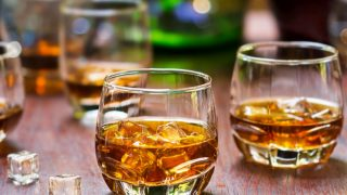 2 glasses of whiskey with ice on a wooden table