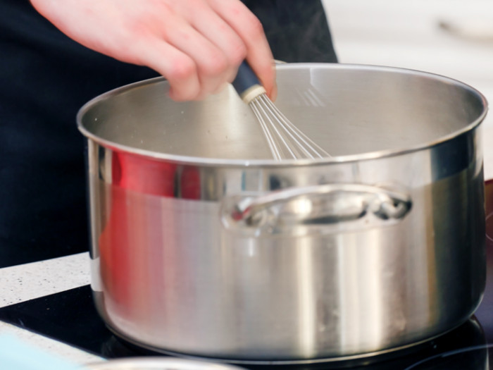 Close-up of someone using a whisk in a pan placed on a hob.