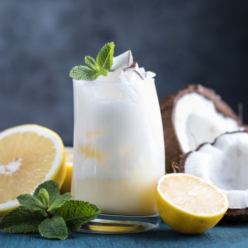 Cocktail drink with pineapple juice, coconut, grapefruit, and lemon and mint in a glass on a blue wooden background