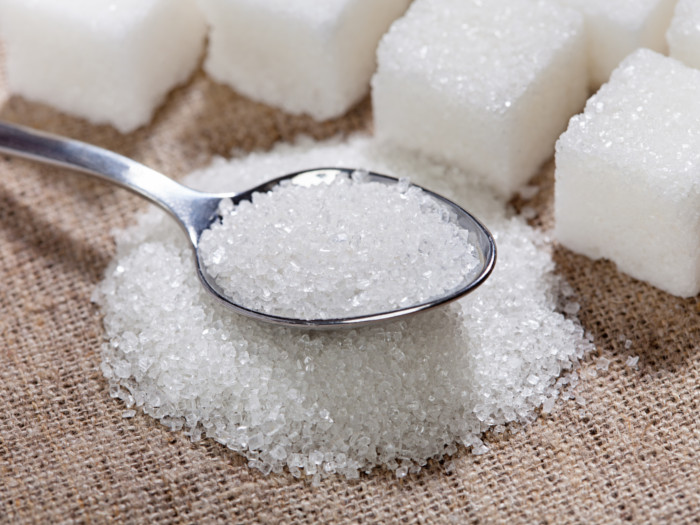 A spoon of sugar with sugar cubes background
