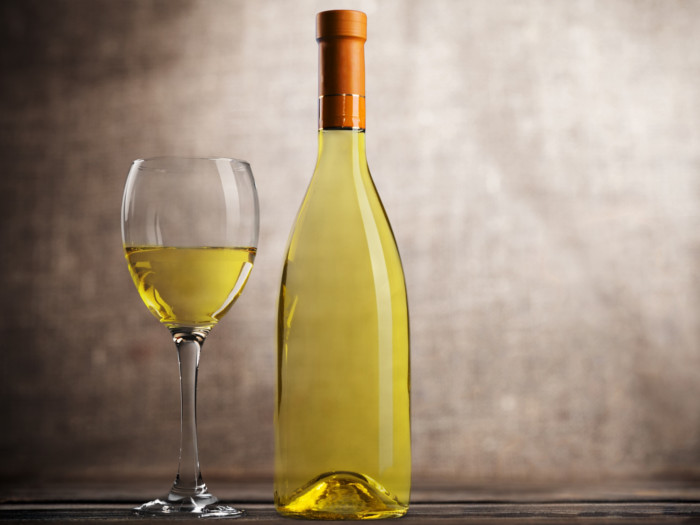 A bottle and glass of wine on a dark background