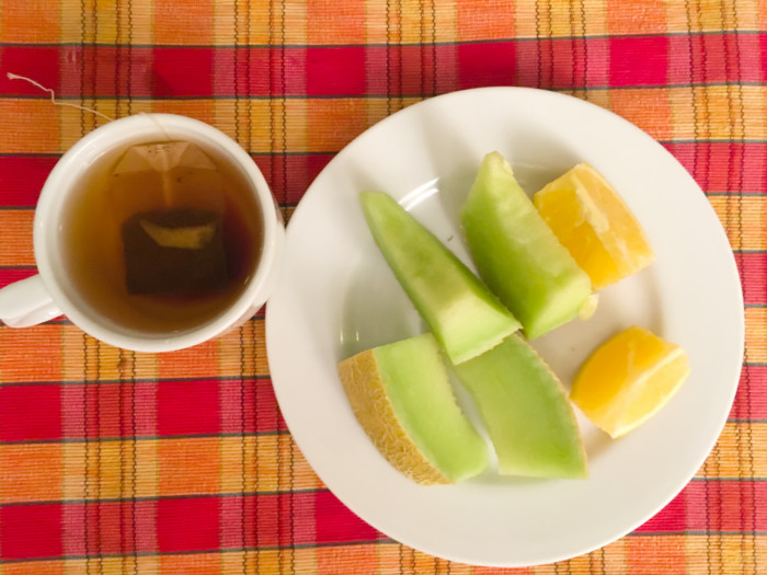 A cup of winter melon tea and a plate of sliced winter melon and lime on a wooden table
