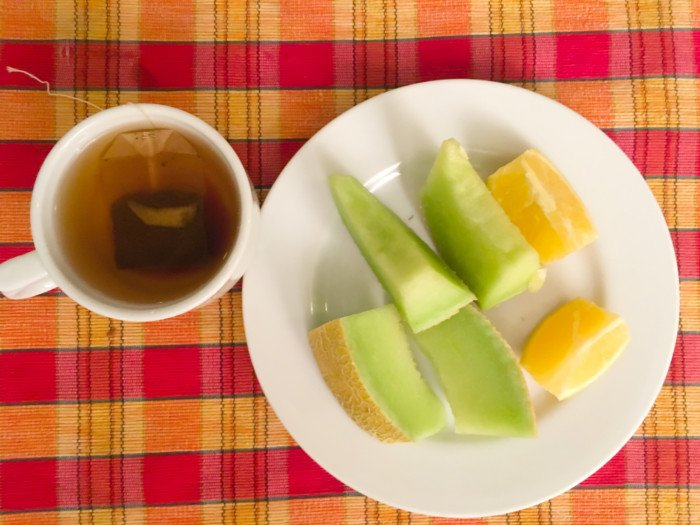 A cup of black tea made with a teabag, a plate of sliced winter melon and lime on a wooden table