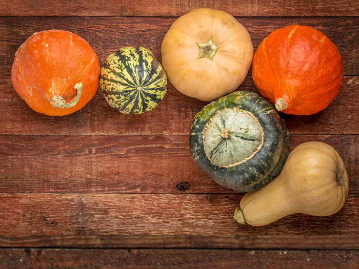 Different types of winter squash such as kabocha, red Kuri, acorn, and butternut squash on a wooden table