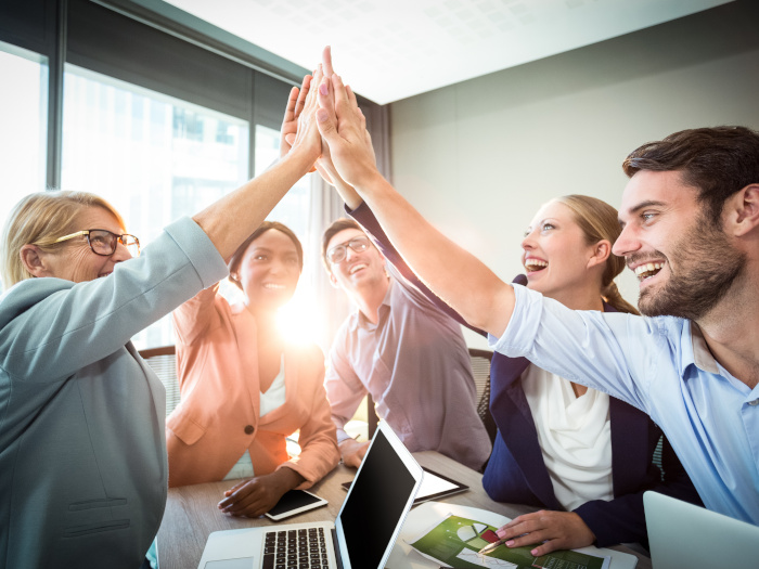 A group of work colleagues giving high-fives to each other in the office