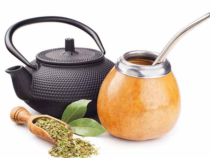 A tea pot and flask of yerba mate tea kept beside a spoon of dried yerba mate tea leaves against a white background