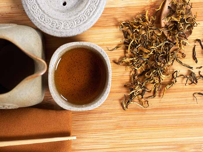A jar and cup of Dainhong or Yunnan tea with a spoon of dried fresh Yunnan leaves on a wooden table