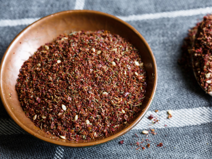 Close up of za'atar spice in a bowl on a grey and white table cloth