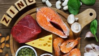Foods rich in zinc (sliced salmon, meat, prawns, garlic, mushrooms, almonds, cashews, spinach, & legumes) on a wooden table